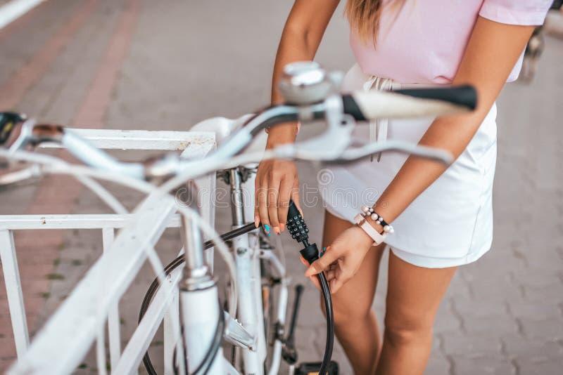 Ein Mädchen schließt ihr Fahrrad im Sommer in der Stadt, einen Beschränkungszaun, ein Verschluss auf dem Rahmen des Fahrrades, Pa stockfotografie