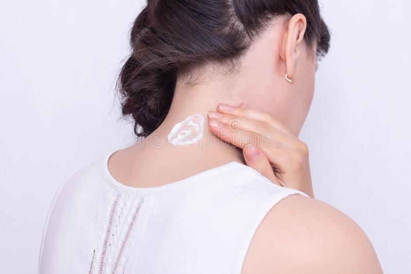 Ein Mädchen schmiert einen Hals mit einer Heilung und einer entzündungshemmenden Salbe, um Muskelsteifheit und die Schmerz, Nahau stockfotos