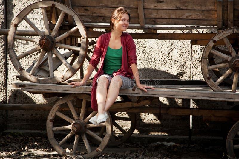 Ein Mädchen sitzt auf einem alten telega stockbilder