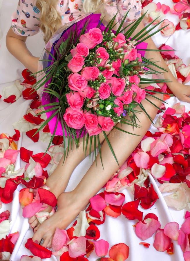 Ein Mädchen sitzt auf einem Bett mit einem rosa Blumenstrauß von Blumen Ein Geschenk für den Feiertag Weibliche Füße stockbilder