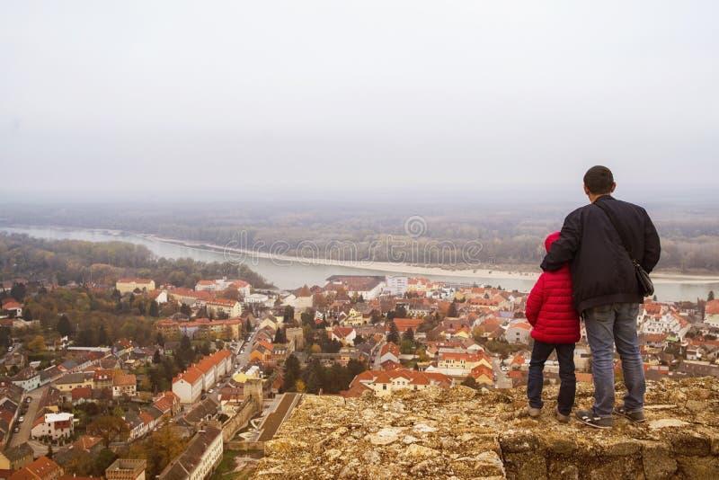 Ein Mädchen sitzt auf einer alten Felsenwand Das Mädchen, das auf den Schritten im alten Schloss sitzt lizenzfreies stockfoto