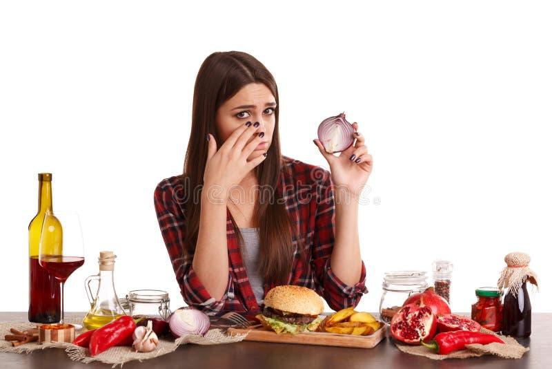 Ein Mädchen sitzt an einem Tisch mit Lebensmittel und hält eine Hälfte von Zwiebeln und von Schreien von ihr Lokalisiert auf Weiß lizenzfreie stockfotografie