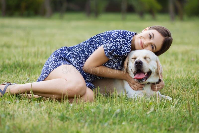 Ein Mädchen spielt mit einem Hund auf dem Gras Ausbildung des Hundes lizenzfreies stockbild