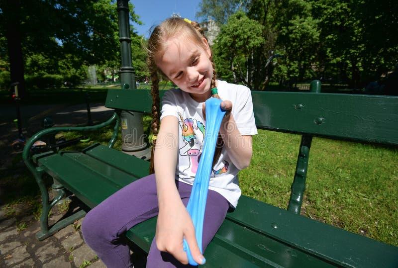 Ein Mädchen spielt mit Schlamm auf der Parkbank Blauer ausdehnender Schlamm in den Händen des Mädchens lizenzfreies stockbild