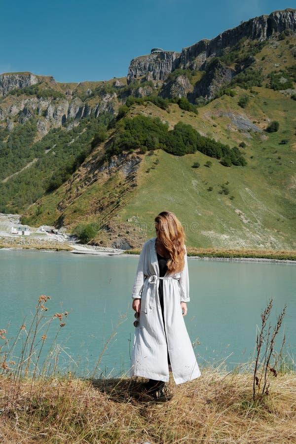 Ein Mädchen steht die Seen im Hintergrund der Berge bereit lizenzfreies stockfoto