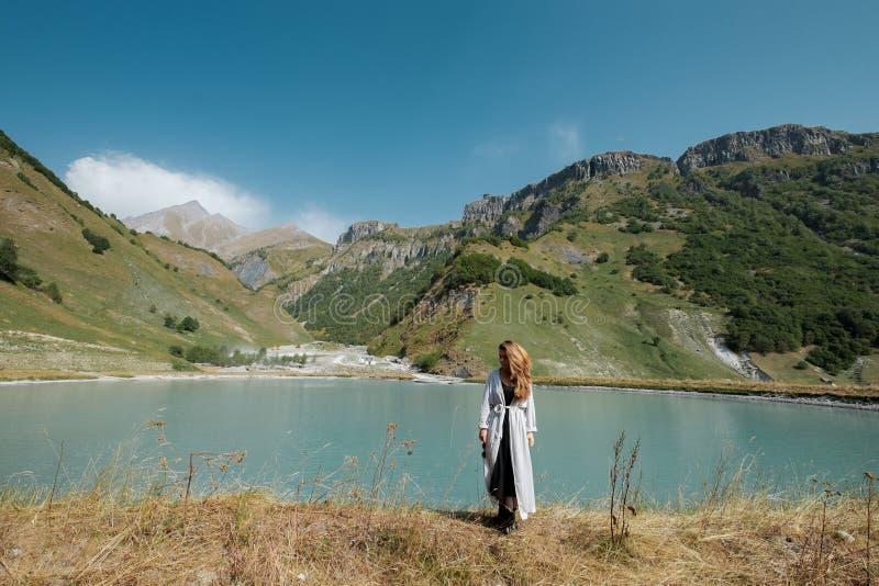 Ein Mädchen steht die Seen im Hintergrund der Berge bereit stockfotos