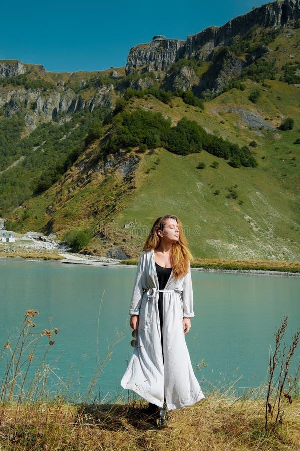 Ein Mädchen steht die Seen im Hintergrund der Berge bereit lizenzfreie stockbilder