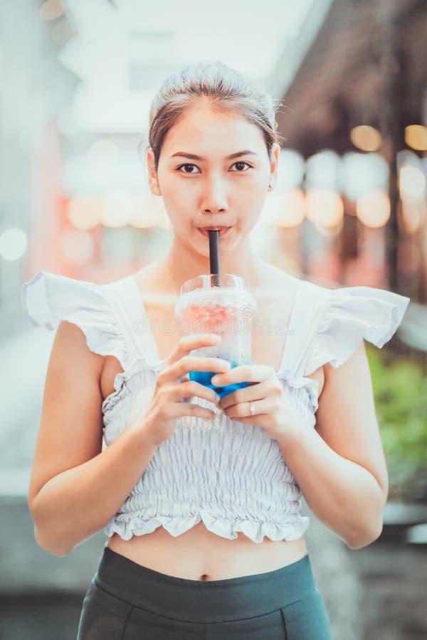 Ein Mädchen trinkt Wasser von einem Glas durch ein Stroh lizenzfreie stockfotos