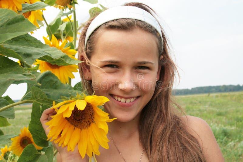 Ein Mädchen und eine Sonnenblume stockbilder