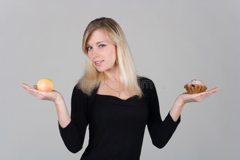 Ein Mädchen wählt zwischen einem Apfel und einem Kuchen lizenzfreies stockbild