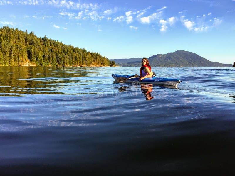 Ein Mädchen, welches das Kayak fahren auf dem schönen und ruhigen Ozeanwasser von Howe Sound, weg von Gambier-Insel, Britisch-Col lizenzfreie stockfotografie