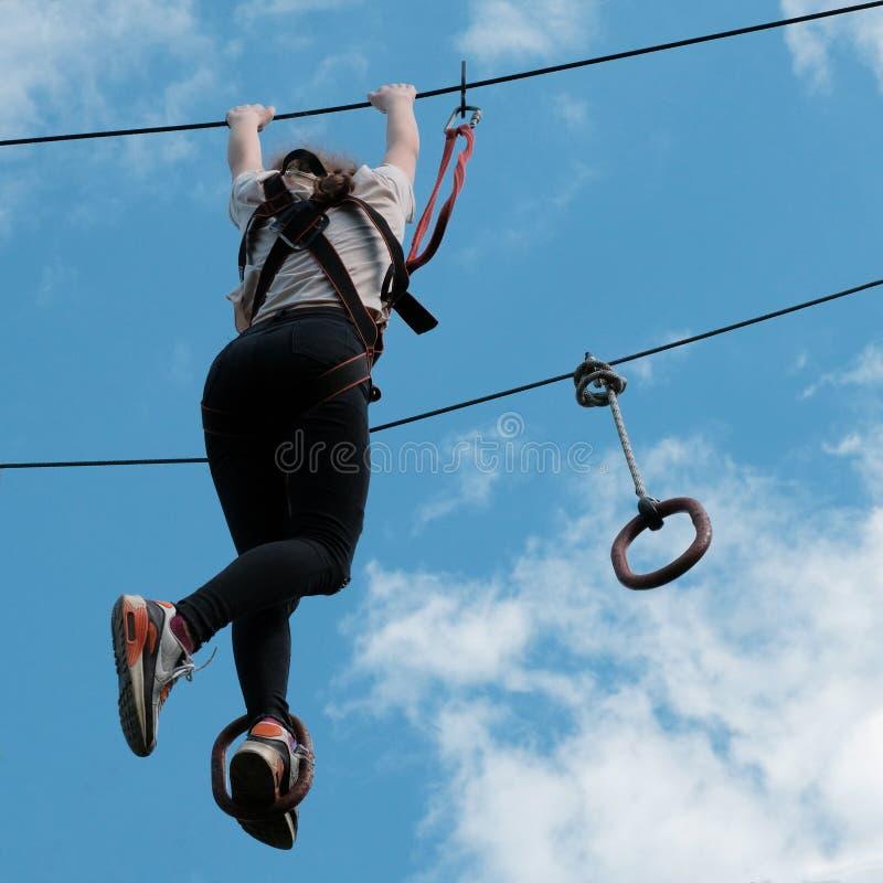 Ein Mädchen, welches das Klettern am Erlebnispark genießt Ziplinie Tätigkeit Quadratisches Bild stockfotografie