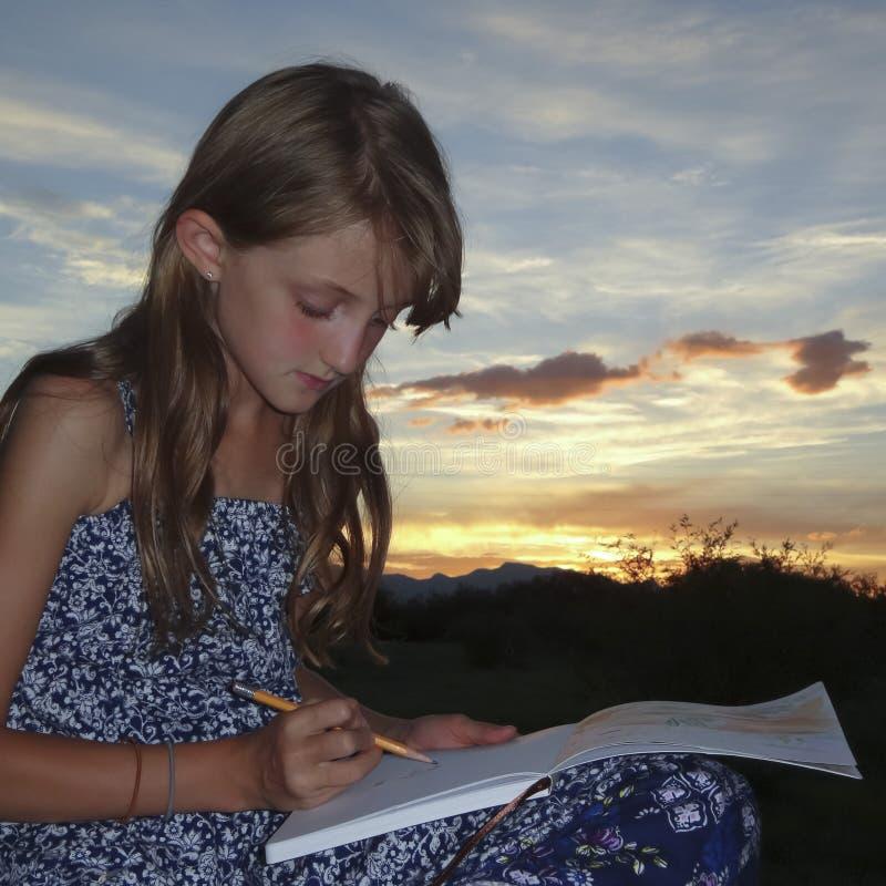 Ein Mädchen zeichnet in eine Skizzen-Auflage lizenzfreies stockbild