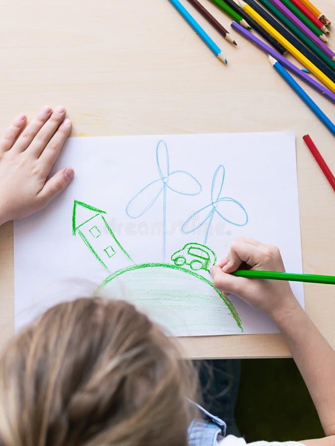 Ein Mädchen zeichnet mit Bleistiften Windkraftanlagen eines Planetenautos des grünen Hauses Konzept von ?kologie und von Umweltsc lizenzfreie stockbilder