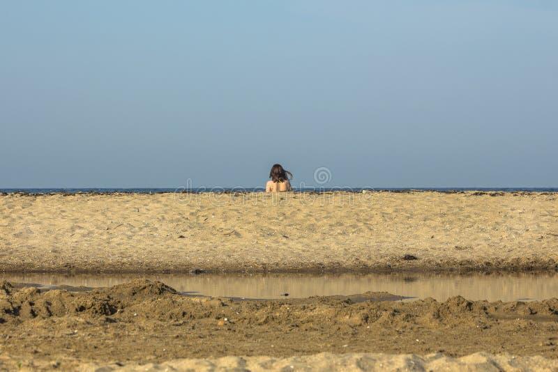 Ein Mädchen zwischen der Flusslagune, dem Sand und dem Meer auf dem Strand von Sinemorets, Bulgarien stockfoto