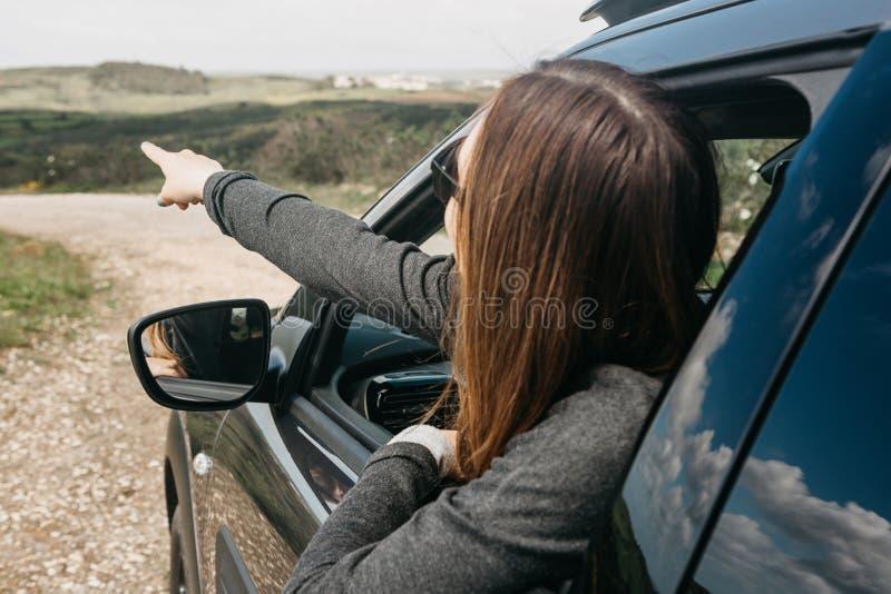 Ein Mädchenfahrer oder ein weiblicher Reisender innerhalb des Autos schaut heraus das Fenster zur Straße stockfotografie