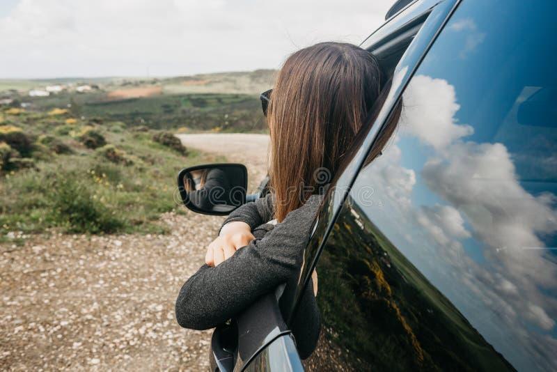 Ein Mädchenfahrer oder ein weiblicher Reisender innerhalb des Autos schaut heraus das Fenster zur Straße stockbild