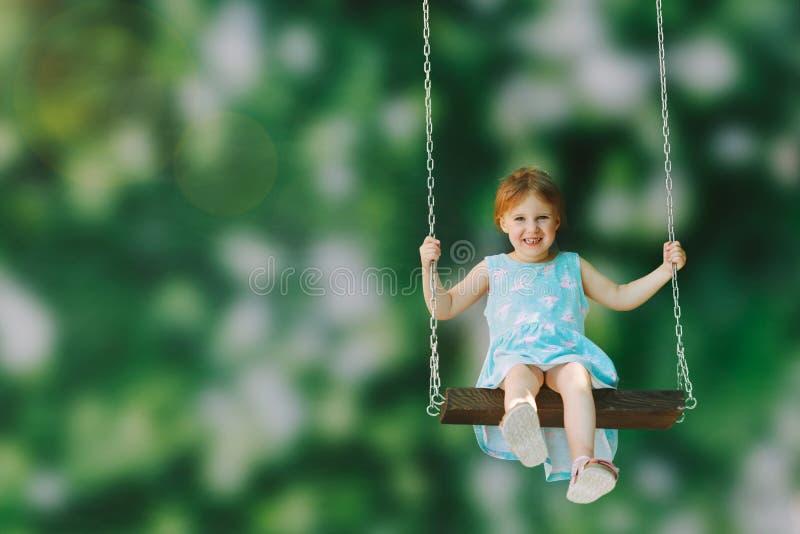 Ein Mädchenreiten auf einem Schwingenfreien lizenzfreie stockbilder