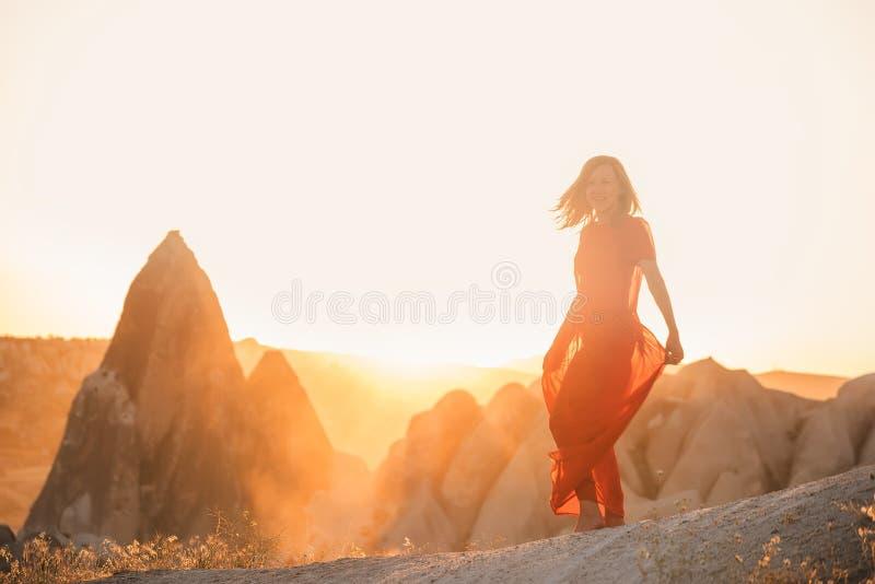 Ein Mädchentanzen in einem roten Kleid im Sonnenlicht gegen den Hintergrund von spitzen Felsen sehr helles künstlerisches Foto Ca lizenzfreie stockbilder