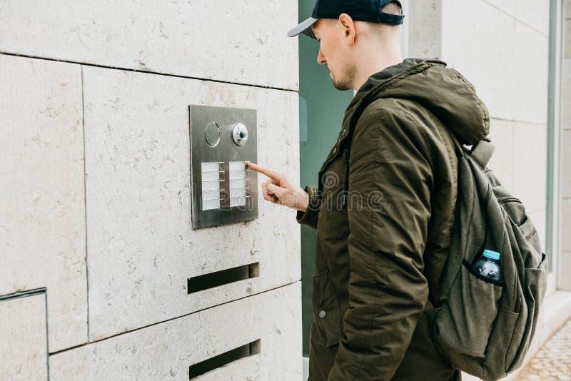 Ein männlicher Anwohner oder ein Tourist klickt an den doorphone Knopf oder nennt die Wechselsprechanlage Ankunft und Anruf von d lizenzfreies stockfoto