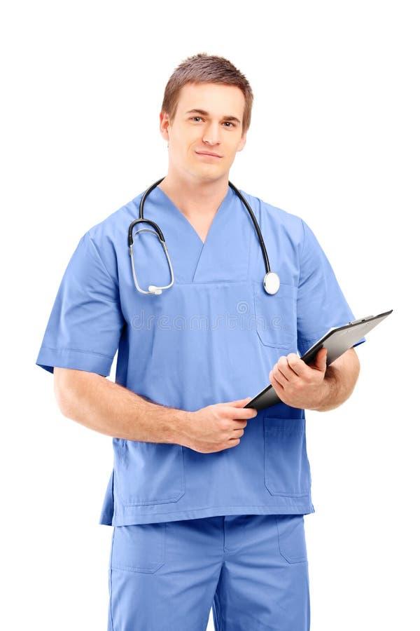 Ein männlicher Arzt in einer Uniform, die mit Klemmbrett in seinem aufwirft stockbild