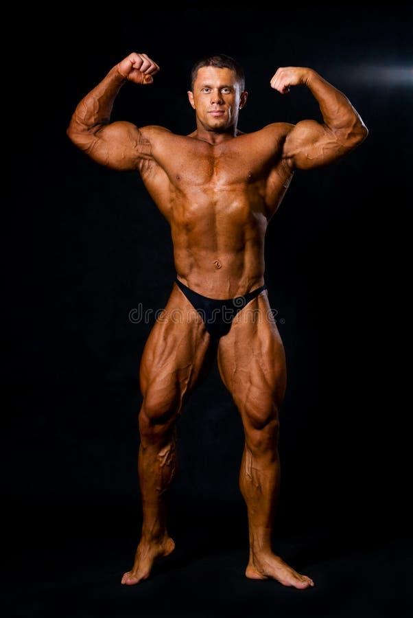 Ein männlicher Bodybuilder, der seine Muskeln biegt. stockfotografie