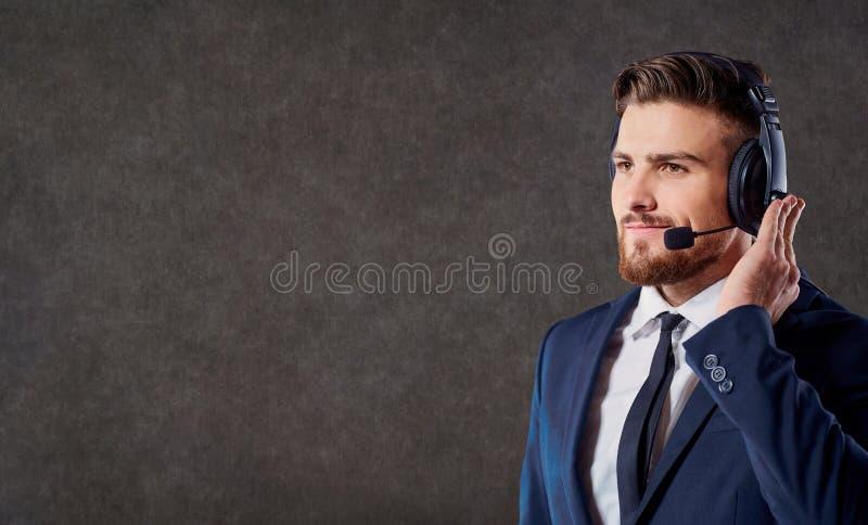 Ein männlicher Call-Center-Betreiber mit Kopfhörer stockfotos