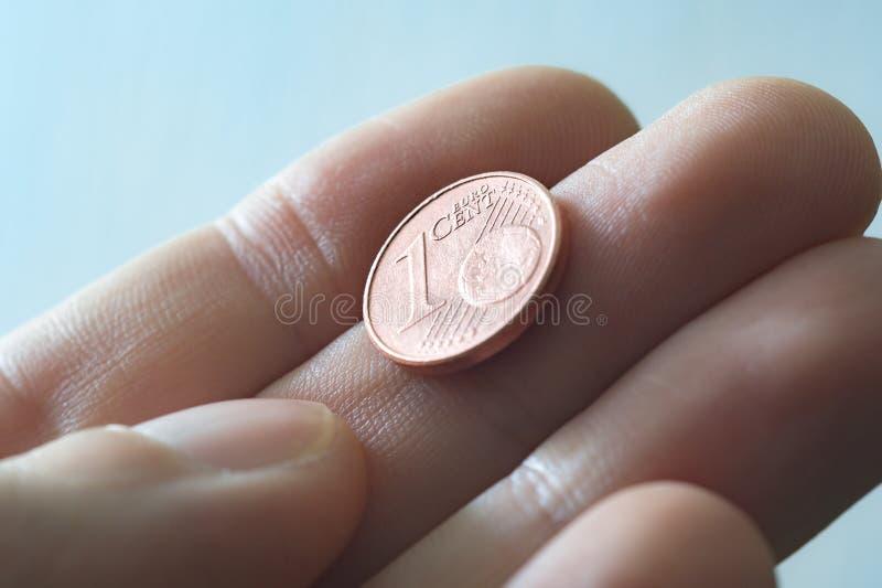 Ein männlicher Daumen und ein Zeigefinger, der eine ein Eurocent Münze greift lizenzfreies stockbild
