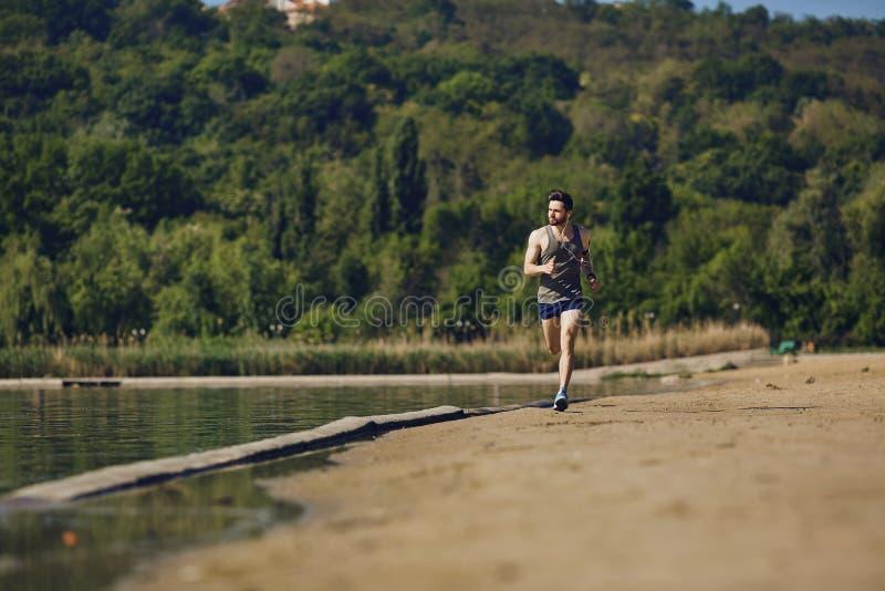 Ein männlicher Läufer läuft entlang die Straße zum Park lizenzfreie stockbilder