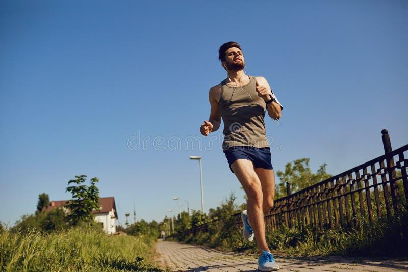 Ein männlicher Läufer läuft entlang die Straße zum Park stockfoto