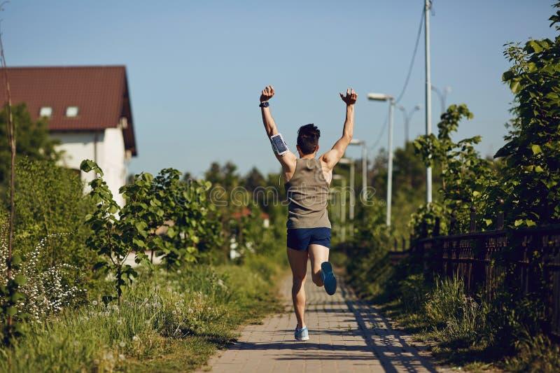 Ein männlicher Läufer läuft mit seinen Armen, die in den Park angehoben werden lizenzfreie stockfotografie