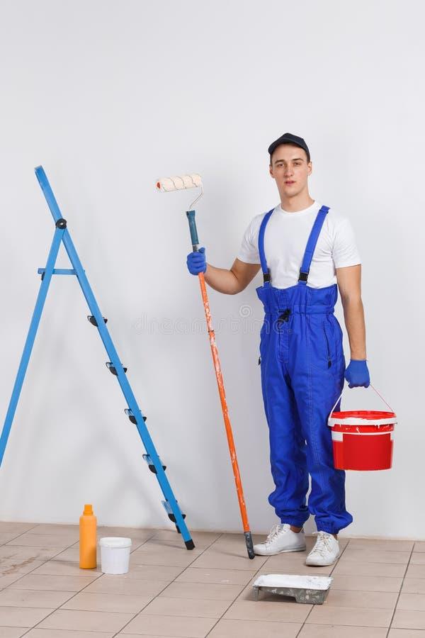 Ein männlicher Maler in der Uniform, einen Eimer mit Farbe und einer Rolle halten stockbilder