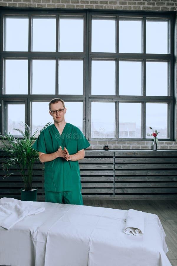 Ein männlicher Massagetherapeut in einer grünen Klage ist lächelnd und fertig zur Arbeit werden stockfotos