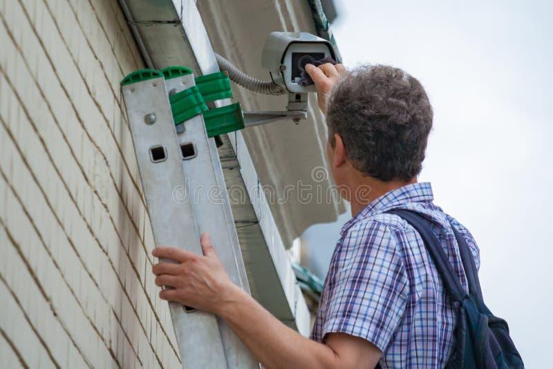 Ein männlicher Techniker erledigt Wartungsarbeiten, indem er eine Sicherheit im Freien kontrolliert und säubert stockbild