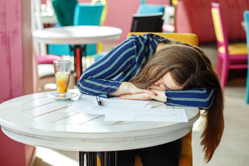 Ein müdes Studentenmädchen schlief beim Vorbereiten für die Prüfung ein T stockbild