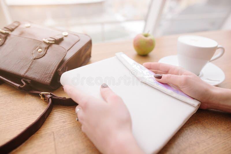 Ein M?dchen h?lt einen Notizblock in ihren H?nden Nahaufnahme eines Notizblockes in den Händen eines Mädchens lizenzfreie stockfotografie