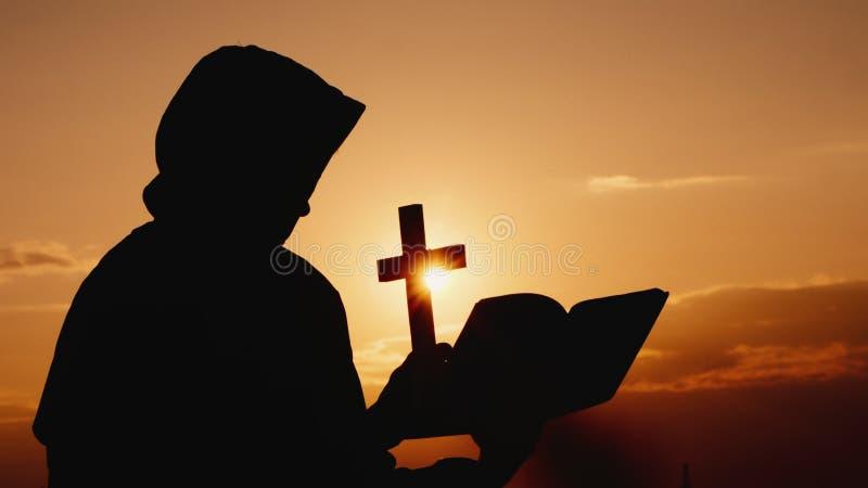 Ein M?nch in einer Haube mit einem Kruzifix in seinen H?nden steht gegen den Hintergrund eines drastischen Himmels bei Sonnenunte lizenzfreie stockbilder