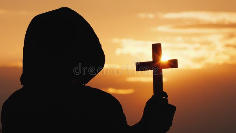 Ein M?nch in einer Haube mit einem Kruzifix in seinen H?nden steht gegen den Hintergrund eines drastischen Himmels bei Sonnenunte stockfotografie