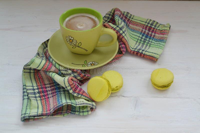 Ein macaron ist ein französischer süßer Meringe-ansässiger Konfektionsartikel, grüne macarons mit Tasse Kaffee stockfoto