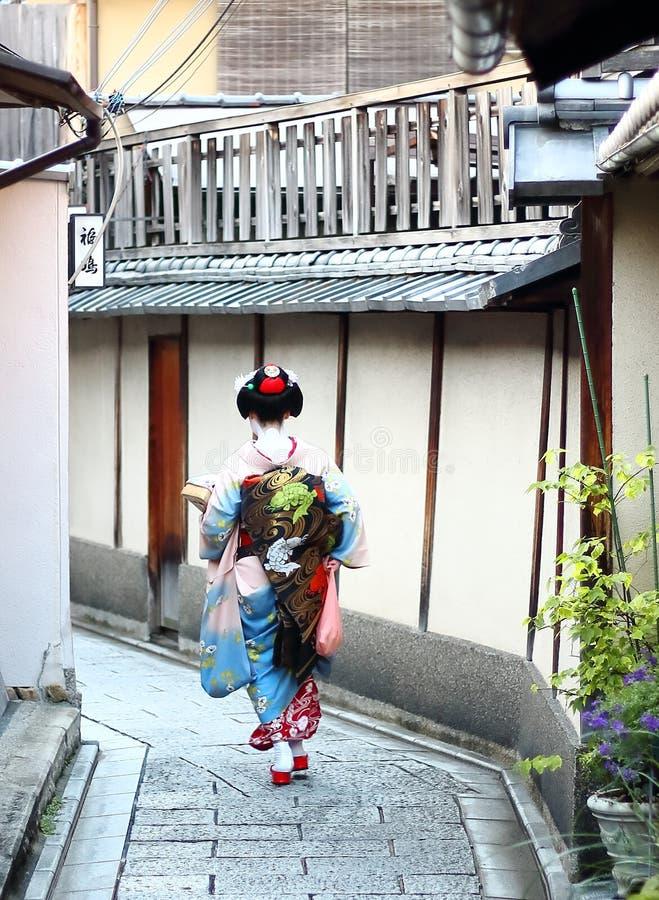 Ein maiko, das hinunter die Straßen von Gions-Nachbarschaft in Kyoto geht lizenzfreies stockbild