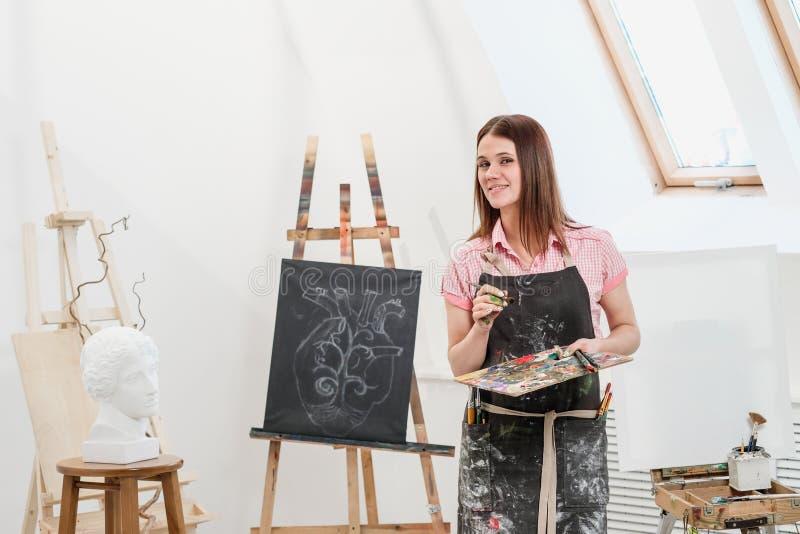 Ein Maler der jungen Frau in einem hellen weißen Studio zeichnet ein Bild auf Segeltuch auf einem Gestell lizenzfreie stockbilder