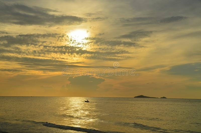 Ein malerischer tropischer, goldfarbener Sonnenaufgang an der Küste in einem gelben Himmel Thailand lizenzfreies stockbild