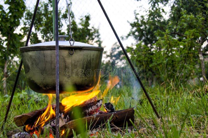Ein man& x27; s-Hand z?ndet ein Feuer unter einer Wanne an, die auf einem Feuer steht lizenzfreies stockbild