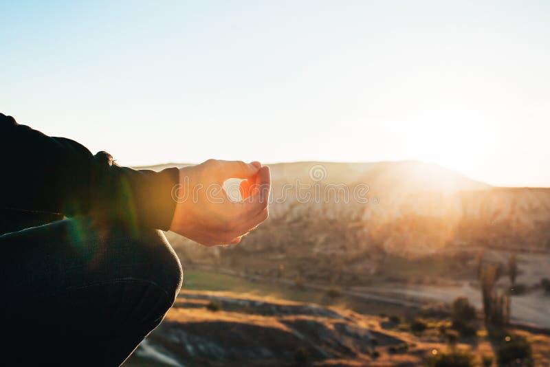 Ein Mann übt Yoga an der Spitze des Berges bei Sonnenaufgang Praxis des Entspannung stockbilder