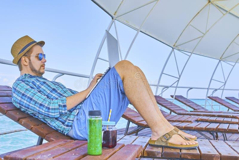 Ein Mann arbeitet im Urlaub lizenzfreie stockbilder