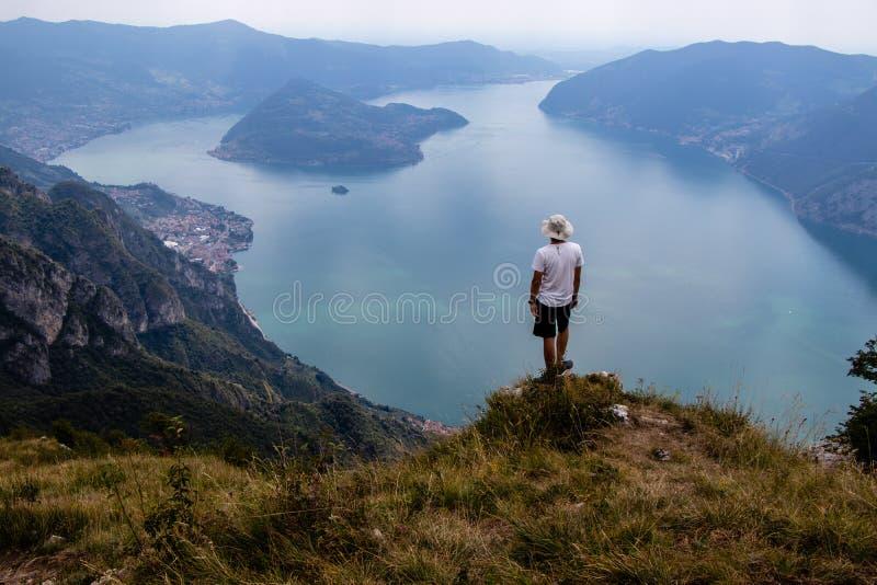 Ein Mann auf einer Klippe in den Bergen nahe bei italienischem alpinem See Iseo a lizenzfreie stockfotografie