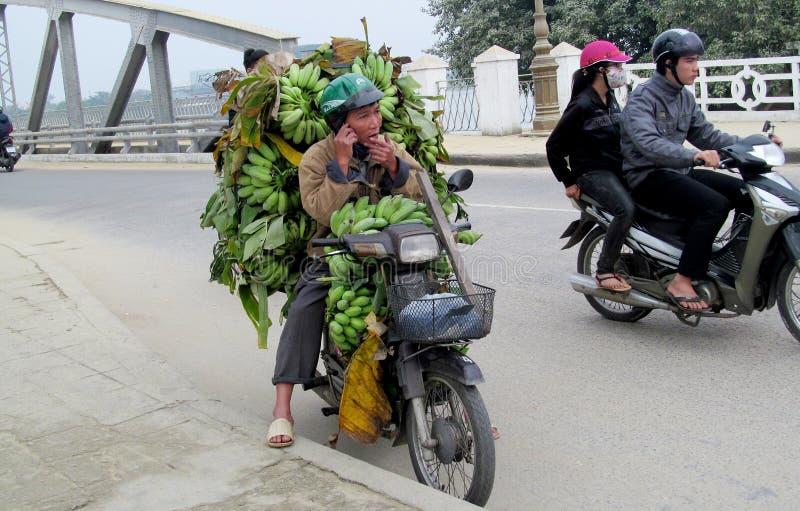 Ein Mann auf Motorrad in Asien mit babanas lizenzfreie stockfotos