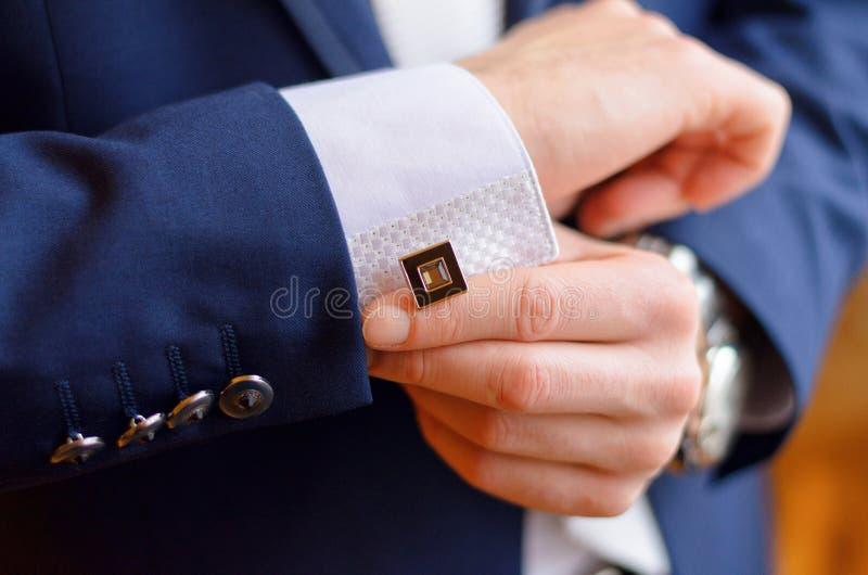 Ein Mann befestigt einen Manschettenknopf stockbilder