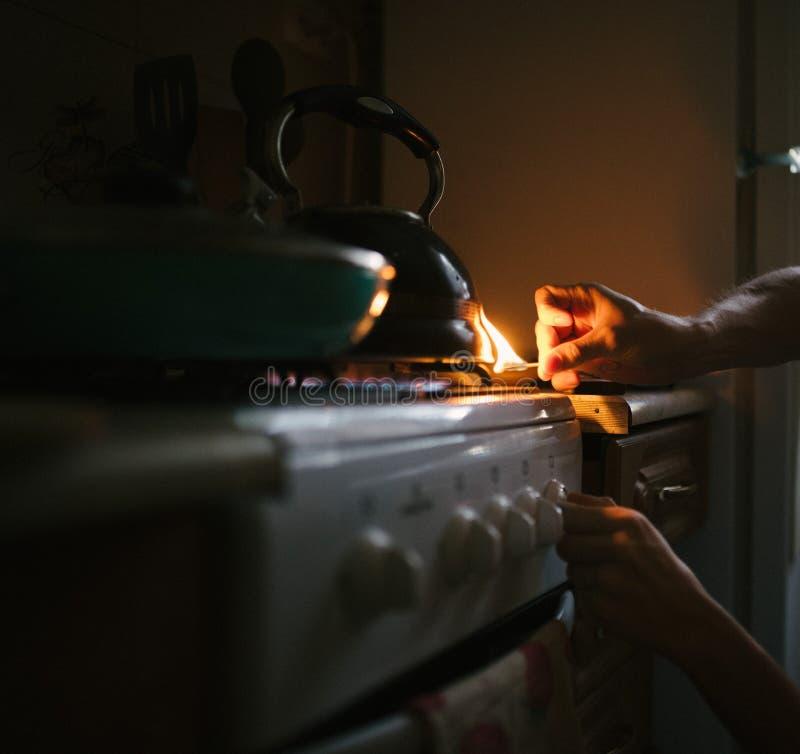 Ein Mann beleuchtet ein Match auf einem Gasherd mit einem Match lizenzfreie stockfotografie