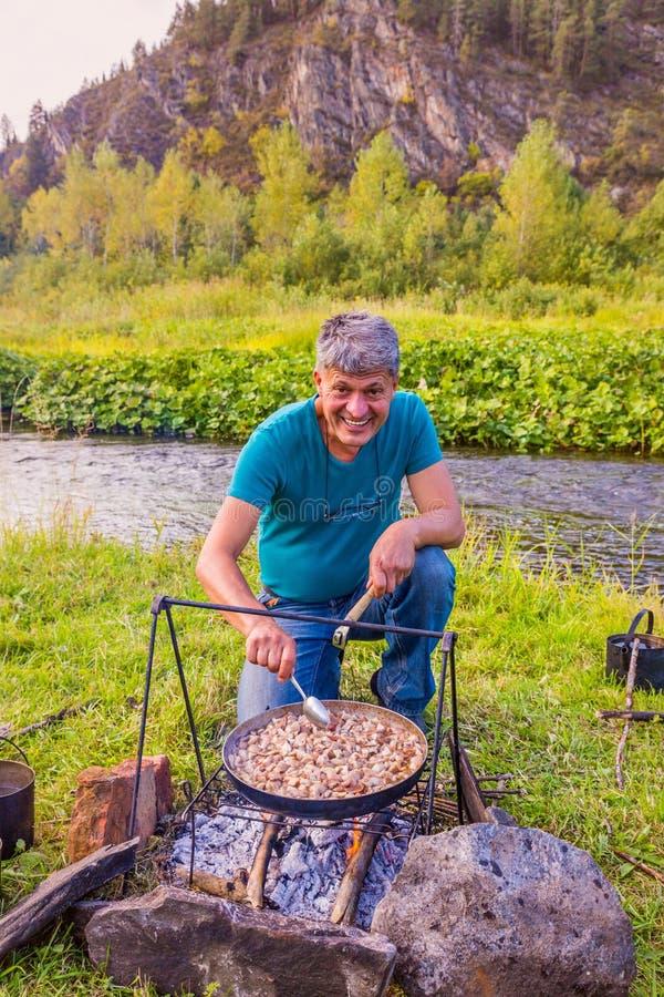 Ein Mann bereitet Pilze auf einem Feuer auf der Bank des Flusses zu lizenzfreie stockbilder